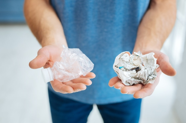 Thorough recycler. the focus being on the hands of a young man in a blue t-shirt holding a crushed plastic bottle in one hand and a crumpled newspaper in another hand