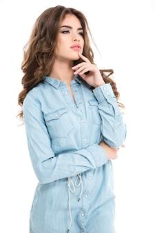 Задумчивая привлекательная молодая женщина с длинными вьющимися волосами в джинсовой рубашке стоит и думает над белой стеной