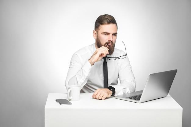 흰 셔츠와 검은 넥타이를 입은 사려깊은 수염이 있는 젊은 사장은 책상에 앉아 노트북으로 일일 보고서를 보고, 새로운 아이디어를 갖고 자신의 전략을 계획하고, 안경을 벗고 있습니다. 실내