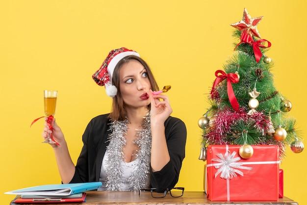 산타 클로스 모자와 고립 된 노란색에 사무실에서 와인을 올리는 새해 장식 정장에 사려 깊은 매력적인 아가씨