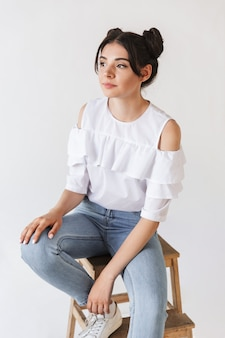 흰색에 고립 된 의자에 앉아있는 동안 우울한 눈으로 옆으로 보이는 더블 빵 헤어 스타일을 가진 사려 깊은 소녀