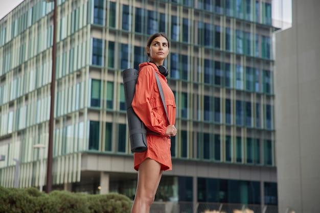 Задумчивая, целеустремленная спортсменка в хорошей физической форме, стройные ноги, одетая в спортивную одежду, несет свернутый фитнес-коврик на плече, позирует на фоне современного здания.