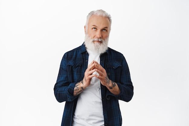 Задумчивый старый стильный мужчина скрещивает пальцы, смотрит вверх и думает, строит планы, строит планы, как злой гений, читая рекламный текст над головой, стоя над белой стеной