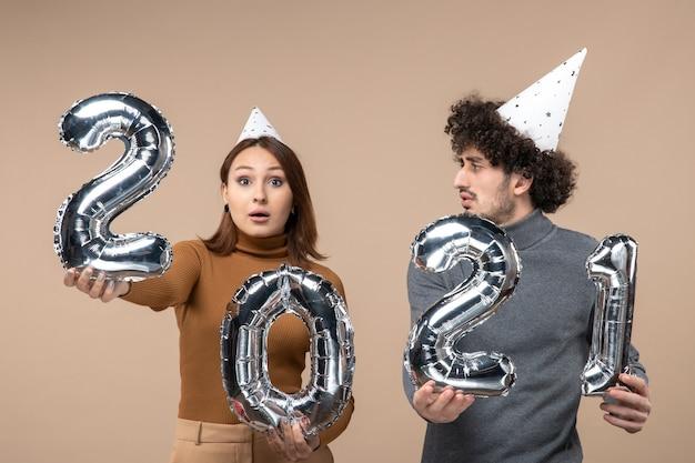 思いやりのある若いカップルは、カメラの女の子のショーと灰色の男と新年の帽子のポーズを着ています