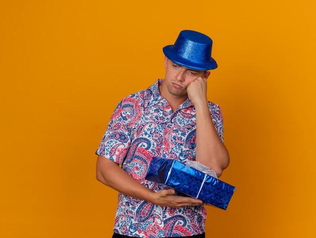 ギフトボックスを保持し、オレンジ色に分離された頬に手を置いて青い帽子をかぶって見下ろしている思慮深い若いパーティーの男