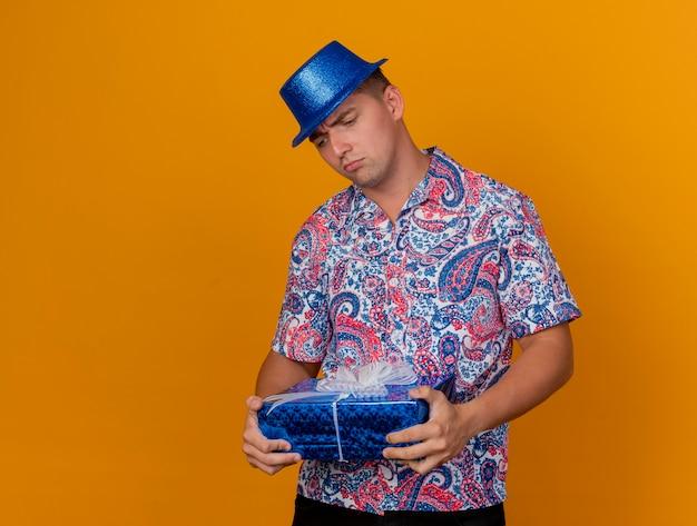 오렌지에 고립 된 선물 상자를 들고 파란색 모자를 쓰고 사려 깊은 젊은 파티 남자