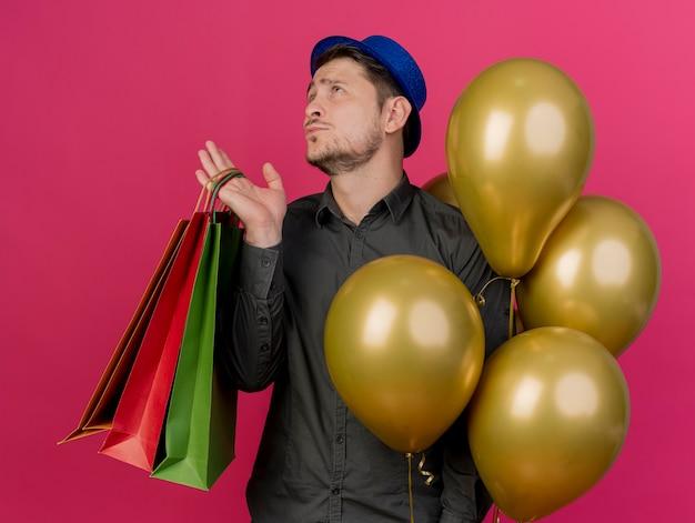 핑크에 고립 된 선물 가방과 함께 풍선을 들고 파란색 모자를 쓰고 사려 깊은 젊은 파티 남자