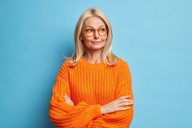 思いやりのある愛らしい金髪の40歳の喜んでいる女性は腕を組んで何かを考えて目をそらし、眼鏡ニットのセーターを着ています。