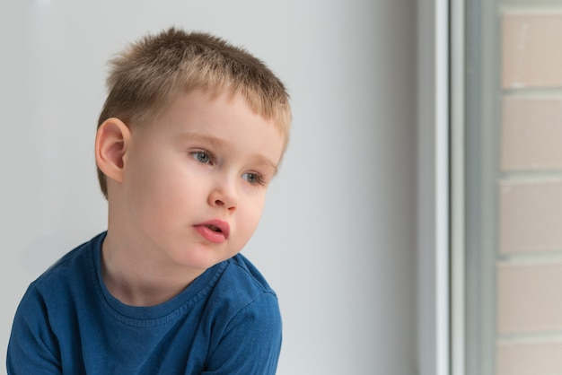 Thoughtful adorable boy in blue shirt looking throw the window
