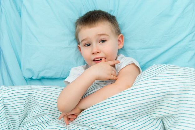 Thoughtful adorable boy in white shirt lays in the bed
