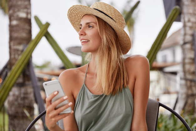 Thoughtful adorable woman in casual clothing, keeps modern smart phone, looks aside, recreate outdoor during summer weather, dreams about something pleasant. people, technology, lifestyle concept