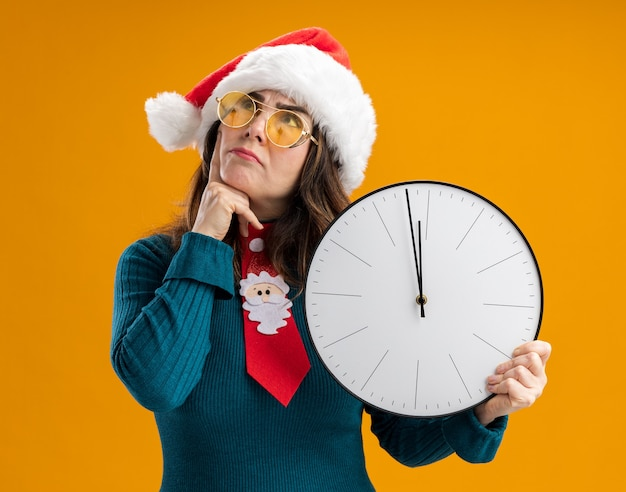 산타 모자와 산타 넥타이와 태양 안경에 사려 깊은 성인 백인 여자 시계를 보유하고 복사 공간이 오렌지 벽에 고립 된 찾고 턱에 손가락을 넣습니다