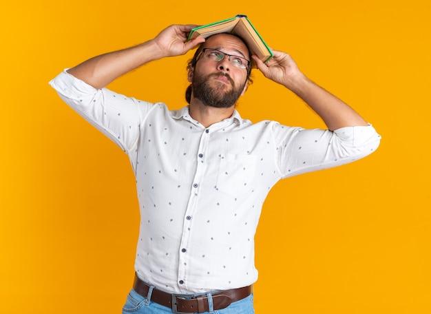 オレンジ色の壁に隔離された頭の上に本を持って眼鏡をかけて思慮深い大人のハンサムな男