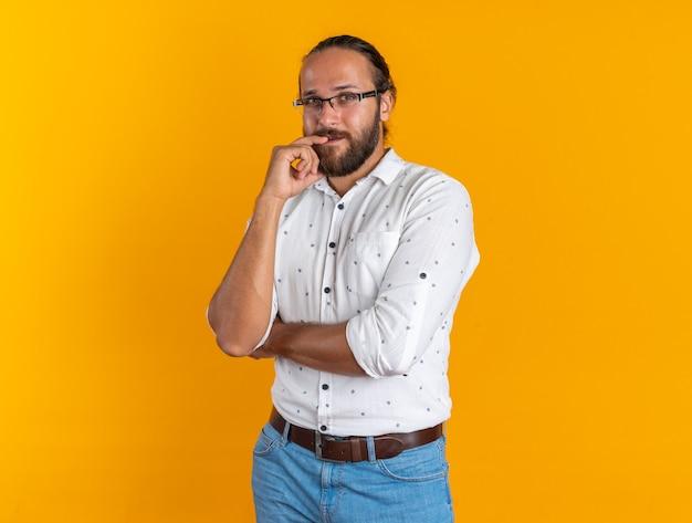 コピースペースでオレンジ色の壁に分離されたカメラを見て、唇に指を保ちながら眼鏡をかけている思いやりのある大人のハンサムな男