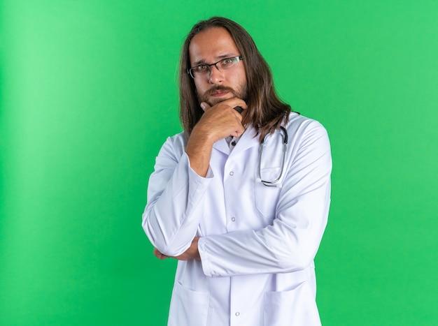 의료 가운과 청진기를 착용한 사려 깊은 성인 남성 의사는 안경을 쓰고 턱에 손을 대고 복사 공간이 있는 녹색 벽에 격리된 카메라를 보고