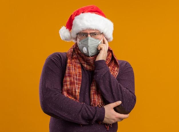 Uomo adulto premuroso che indossa occhiali maschera protettiva e cappello santa con sciarpa intorno al collo guardando la telecamera facendo pensare gesto isolato su sfondo arancione