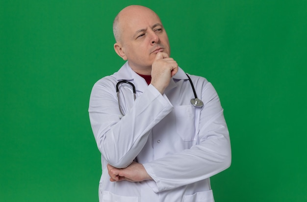 Thoughtful adult slavic man in doctor uniform with stethoscope putting hand on his chin and looking at side