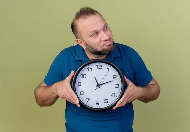 Thoughtful adult slavic man holding clock looking at side
