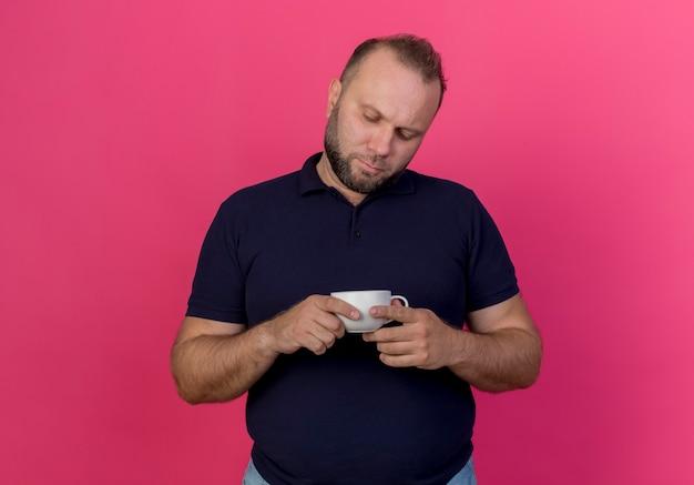 Uomo slavo adulto premuroso che tiene e che esamina tazza isolata