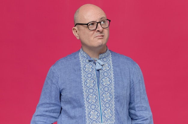 Задумчивый взрослый славянский мужчина в синей рубашке в оптических очках смотрит вверх