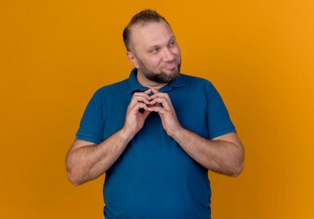 Uomo slavo adulto premuroso che tiene le mani insieme guardando a lato