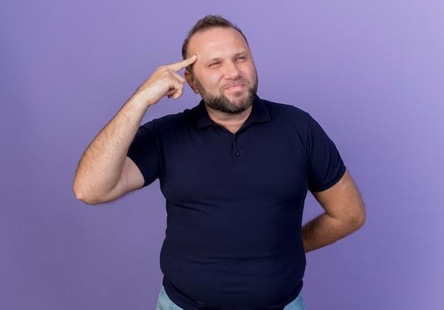Задумчивый взрослый славянский мужчина смотрит в сторону, кладет палец на висок, держа руку за спиной изолированной