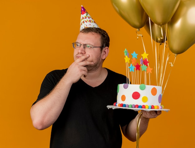 Thoughtful adult slavic man in optical glasses wearing birthday cap puts hand on chin holds helium balloons and birthday cake looking at side