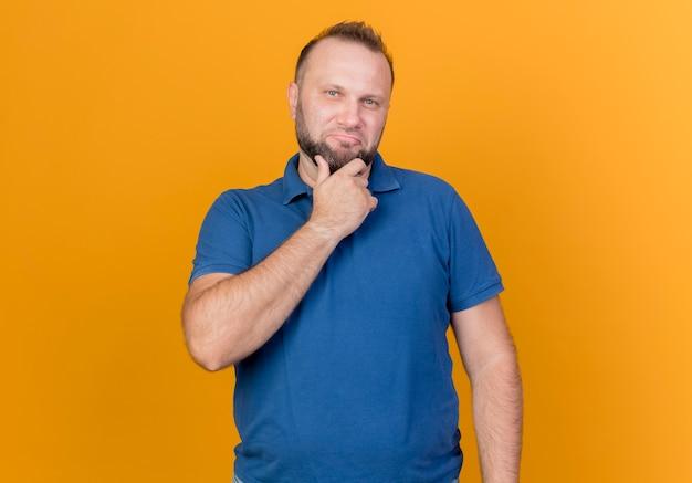 Uomo slavo adulto premuroso che tocca il mento che sembra isolato