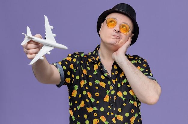 검은 모자를 쓰고 선글라스를 끼고 비행기 모델을 들고 올려다보는 사려 깊은 성인 슬라브 남자