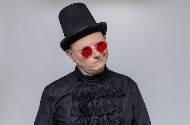 Thoughtful adult slavic man with top hat and with sunglasses in black gothic shirt looking up