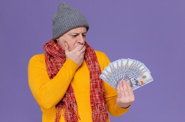 冬の帽子と首にスカーフを持ってお金を持って見ている思いやりのある大人のスラブ人