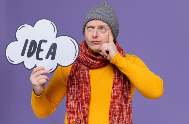 Thoughtful adult slavic man with winter hat and scarf around his neck holding idea bubble