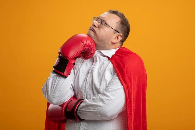 Вдумчивый взрослый славянский супергерой в красном плаще в очках и боксерских перчатках положил руку на подбородок с закрытыми глазами, изолированными на оранжевом фоне с копией пространства
