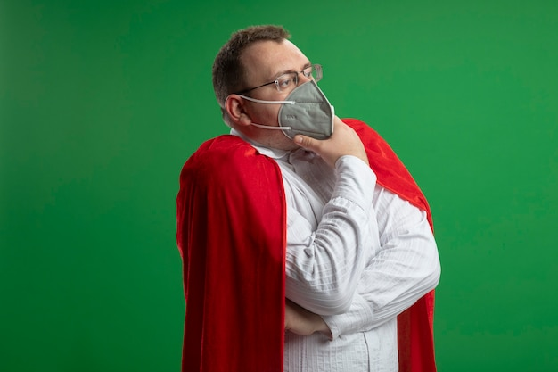 복사 공간 녹색 벽에 고립 된 똑바로 감동 턱을 찾고 안경과 보호 마스크를 착용하는 빨간 망토에 사려 깊은 성인 슬라브 슈퍼 히어로 남자