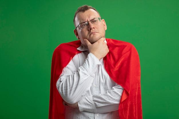 Considerato adulto supereroe slavo uomo in mantello rosso con gli occhiali toccando il mento guardando il lato isolato su sfondo verde con spazio di copia