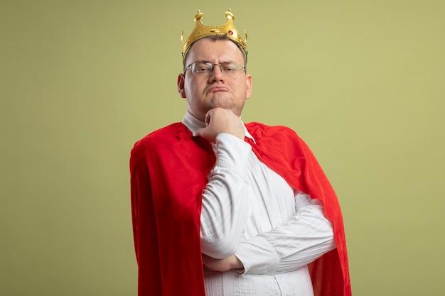 Uomo adulto premuroso del supereroe in mantello rosso con gli occhiali e corona che mette la mano sotto il mento guardando la parte anteriore isolata sulla parete verde oliva