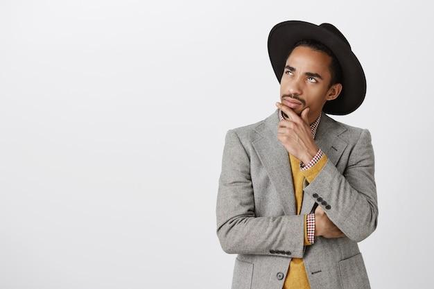 Задумчивый афро-американский мужчина в костюме принимает решение, касается подбородка и смотрит в левый верхний угол, обдумывая выбор