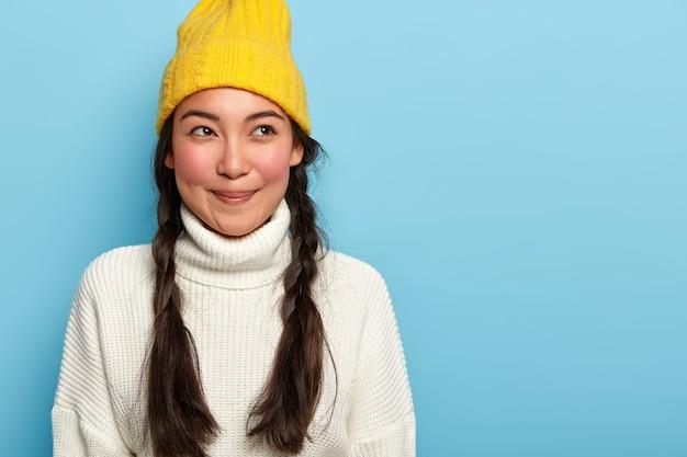 Premurosa e seducente giovane donna asiatica con un sorriso piacevole, ha due trecce scure, vestita in abito invernale, isolato su sfondo blu, esprime un atteggiamento affascinante