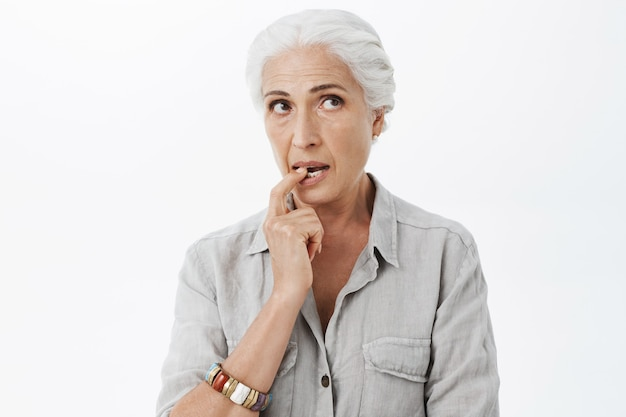 Задумчивая и мечтательная милая пожилая женщина кусает палец и смотрит в правый верхний угол