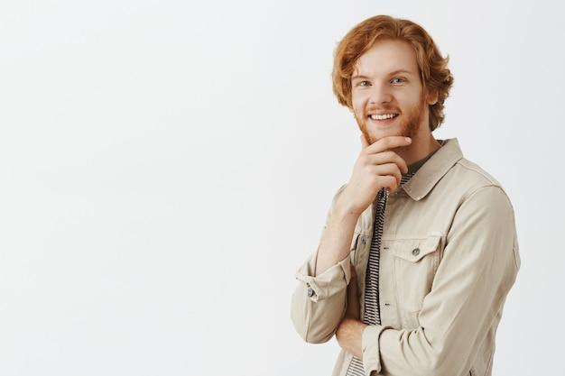 Задумчивый и заинтригованный рыжий бородатый парень позирует на фоне белой стены