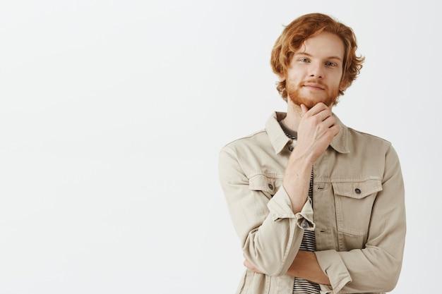 白い壁に向かってポーズをとる思慮深く興味をそそられるひげを生やした赤毛の男