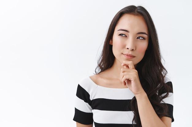Задумчивая и хитрая молодая азиатская брюнетка в полосатой футболке, касаясь подбородка и глядя в сторону с подозрительным, задумчивым выражением лица, прищурившись на вопрос, что-то подсчитывая или принимает решение