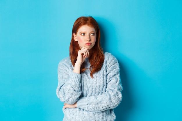 思慮深く、動揺している赤毛の女の子が正しく見え、解決策を熟考し、青い背景に対してセーターに立っています。