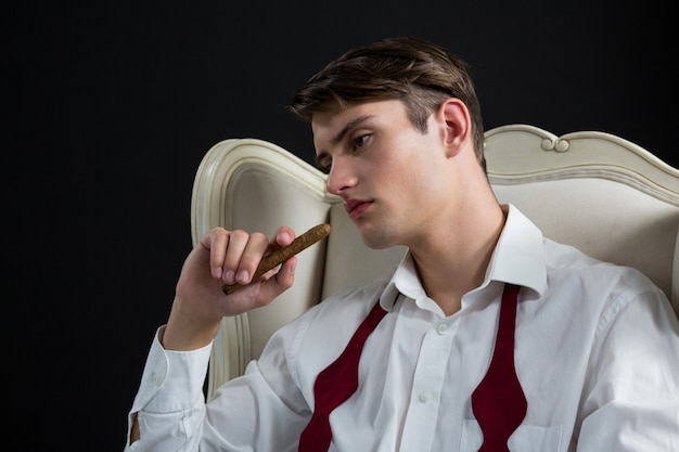 Thoughtful androgynous man sitting on chair with cigar