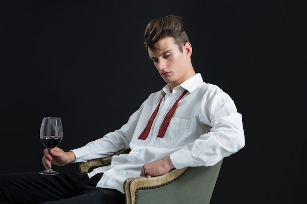 Thoughtful androgynous man sitting on chair with glass of wine