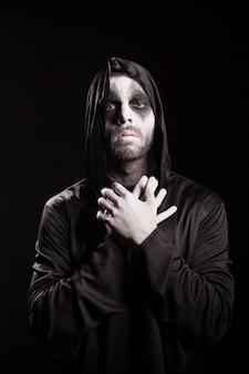 黒の背景に思いやりのある死の天使。ハロウィーンの衣装。