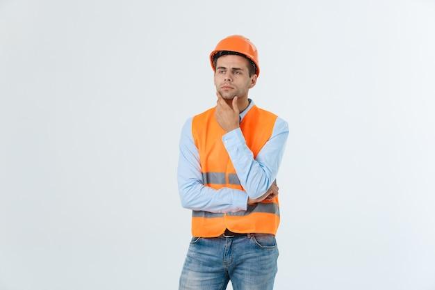 思慮深い建築家またはエンジニアの男は灰色の背景に対して真剣に考えています