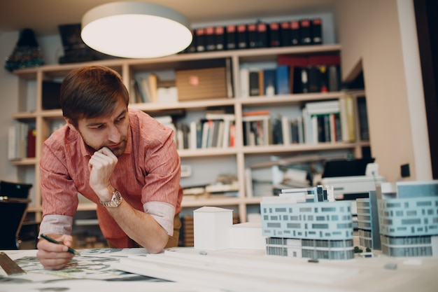 Thoughtful architect with blueprints and layout design project at office