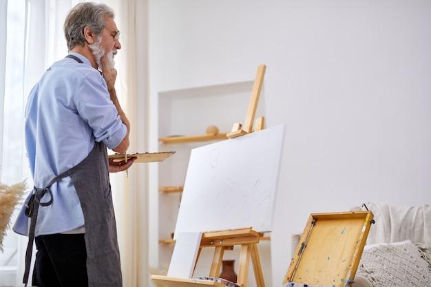 이젤에 캔버스 뒤에 서있는 사려 깊은 예술가 남자, 묵상, 무엇을 그릴 지 생각