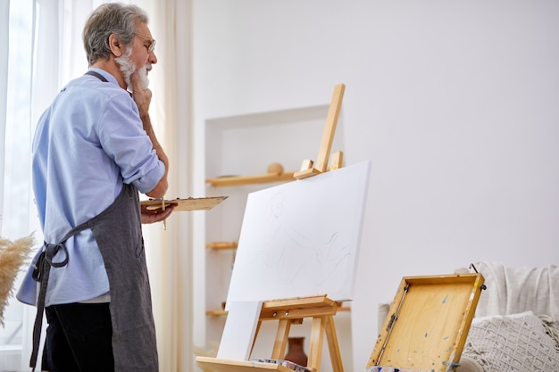 Thoughtful artist man standing behind canvas on easel, in contemplation, think what to draw
